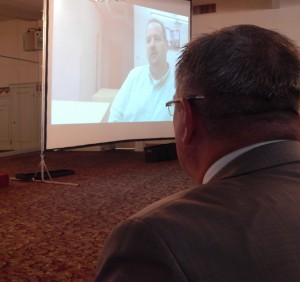 "Superintendent James F. Scully watches a video during the annual day-before-school staff gathering at DiBurro's, Ward Hill. The title of the video is ""Getting Better"" and recounts improvements made in the school district over the past year."