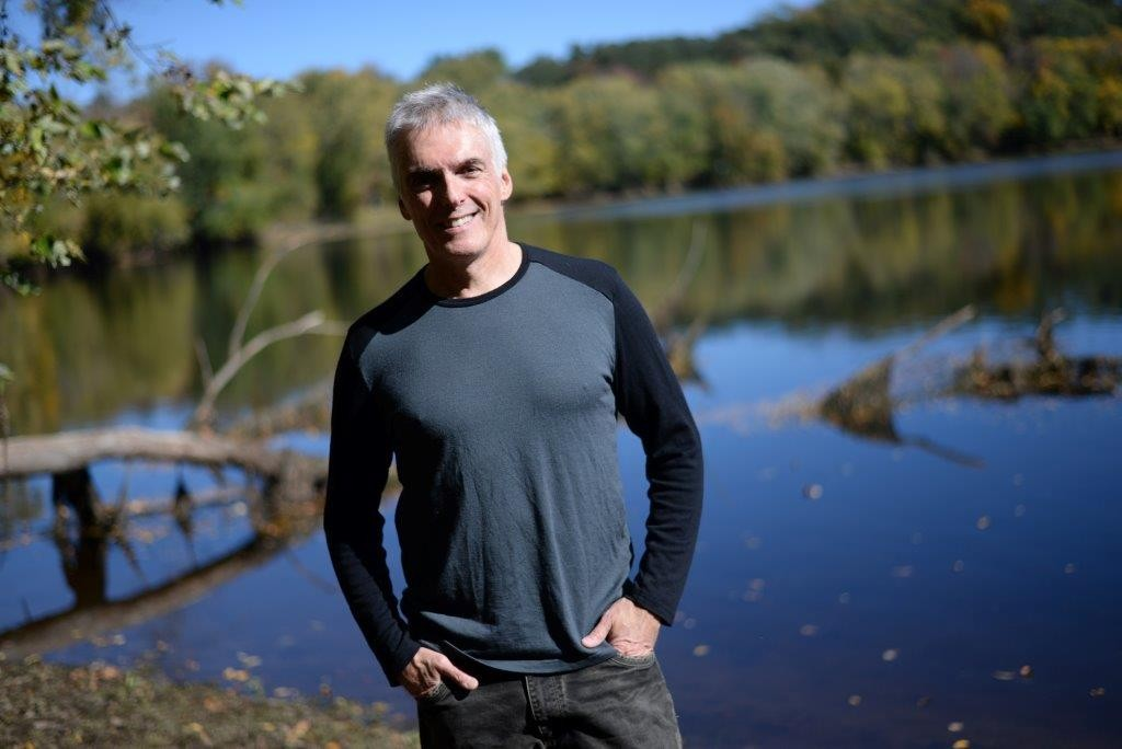 Author Jay Atkinson stands on the banks of the Merrimack River.